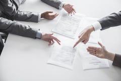 Quattro genti di affari che discutono e che gesturing intorno ad una tavola nel corso di una riunione d'affari, mani soltanto Immagine Stock Libera da Diritti
