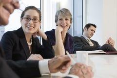 Quattro genti di affari che si incontrano in una sala per conferenze. Immagini Stock Libere da Diritti