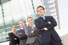 Quattro genti di affari che si levano in piedi all'aperto sorridenti Fotografia Stock