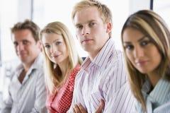 Quattro genti di affari che si siedono all'interno sorridere Fotografia Stock