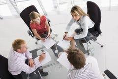 Quattro genti di affari in una sala del consiglio Immagine Stock Libera da Diritti