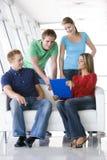 Quattro genti in ingresso che indicano a sorridere dei appunti Fotografia Stock
