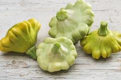 Quattro gialli e patissons verdi della zucca pattypan sulla tavola di legno del fondo bianco Concetto di agricoltura fotografie stock libere da diritti