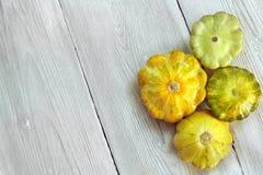 Quattro gialli e zucche verdi del cespuglio su fondo di legno bianco Giardino, agricoltura e concetto di azienda agricola fotografia stock libera da diritti