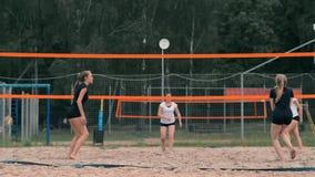 Quattro giocatori di pallavolo delle ragazze giocano sulla spiaggia di estate che partecipano al torneo al rallentatore sulla sab archivi video