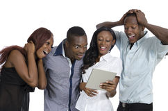 Quattro giovani africani con divertiresi del PC della compressa Fotografia Stock Libera da Diritti