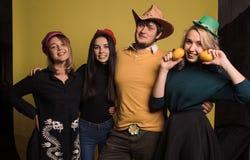 Quattro giovani amici che stanno insieme, abbraccianti, ridenti e sorridenti Lo studio sparato nella parete gialla Fotografia Stock Libera da Diritti
