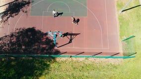Quattro giovani che giocano pallacanestro sul campo sportivo nella via video d archivio