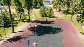 Quattro giovani che giocano pallacanestro sul sportivo nell'aria aperta archivi video