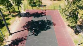 Quattro giovani che giocano pallacanestro sulla corte nell'aria aperta stock footage