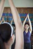Quattro giovani donne che allungano e che fanno yoga, sopra la vista della spalla Fotografie Stock