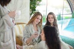 Quattro giovani donne che bevono tè alla località di soggiorno di stazione termale Immagini Stock