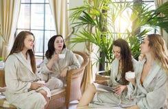 Quattro giovani donne che bevono tè alla località di soggiorno di stazione termale Fotografia Stock Libera da Diritti