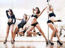 Quattro giovani donne sexy di ballo del palo Immagine Stock