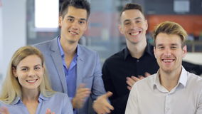 Quattro giovani e bella congratulazioni degli impiegati di concetto, strizzatina d'occhio di applauso e sorriso alzanti le dita i archivi video