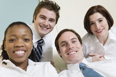 Quattro giovani genti di affari sorridenti. Immagine Stock Libera da Diritti