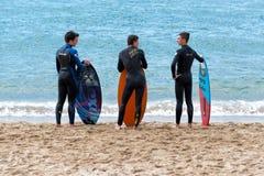 Quattro giovani surfisti davanti al mare immagini stock