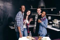 Quattro il giovane e donna si divertono a casa la cucina immagine stock