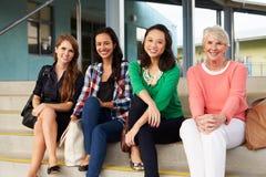 Quattro insegnanti femminili che si siedono sui punti all'entrata della scuola Immagini Stock