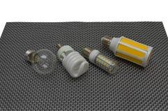 Quattro lampade elettriche su un fondo scuro, una lampada di incandescenza, fluorescente, LED fotografia stock libera da diritti