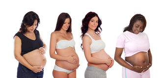 Quattro mamme che segnano la sua pancia Immagini Stock
