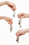 Quattro mani che tengono i mazzi di chiavi Fotografia Stock Libera da Diritti