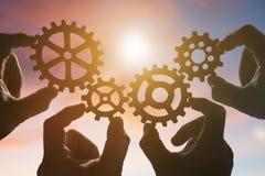 Quattro mani raccolgono un puzzle degli ingranaggi, contro lo sfondo del cielo al tramonto immagini stock