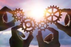 Quattro mani raccolgono un puzzle degli ingranaggi, contro lo sfondo del cielo al tramonto immagini stock libere da diritti