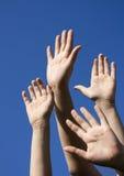 Quattro mani umane sollevate in su fotografia stock libera da diritti