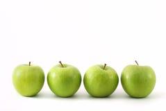 Quattro mele verdi in una riga Fotografia Stock