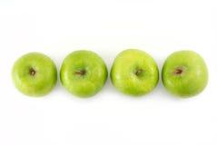 Quattro mele verdi in una riga Immagine Stock