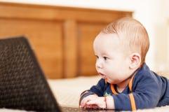 Quattro mesi di bambino con il computer portatile Immagine Stock