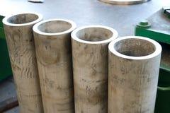 Quattro metallo, ferro, tubi grigi che stanno in una fila alla fabbrica, negozio Il concetto delle parti fabbricanti fotografia stock libera da diritti