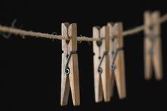 Quattro mollette da bucato di legno su un cavo Fotografia Stock