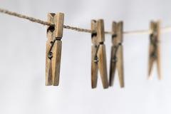 Quattro mollette da bucato di legno su un cavo Fotografie Stock Libere da Diritti