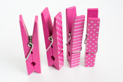 Quattro mollette per il bucato rosa con i modelli di divertimento che stanno su Fron ad angolo Immagini Stock