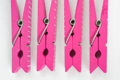 Quattro mollette per il bucato rosa con i modelli di divertimento hanno lanciato la vista superiore Fotografia Stock