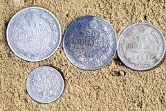 Quattro monete sulla sabbia, vecchie monete d'argento della Russia dello XVIII secolo immagine stock