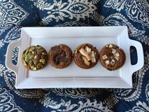 Quattro muffin della zucca un vassoio bianco del servizio su un blu e su un bianco hanno modellato il fondo fotografie stock