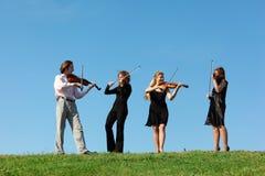 Quattro musicisti giocano i violini contro il cielo Fotografie Stock Libere da Diritti