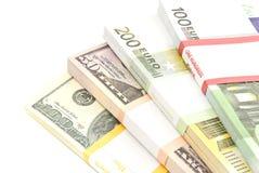 Quattro pacchetti degli euro e dei dollari di banconote Immagini Stock