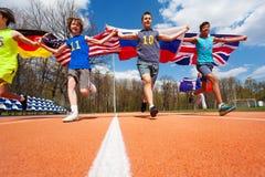 Quattro partecipanti della corsa internazionale con le bandiere Immagine Stock