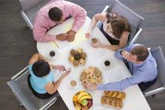 Quattro persone di affari che mangiano alla tabella della sala del consiglio Fotografia Stock Libera da Diritti