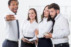 Quattro persone di affari che prendono un selfie fotografia stock libera da diritti