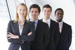 Quattro persone di affari che si levano in piedi nel sorridere del corridoio Fotografia Stock