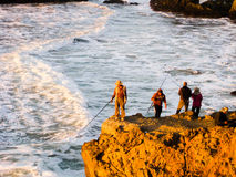 Quattro pescatori sulla scogliera fotografie stock libere da diritti