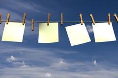 Quattro pezzi di carta in bianco che appendono su una corda Fotografie Stock Libere da Diritti