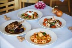 Quattro piatti deliziosi al ristorante Fotografie Stock Libere da Diritti