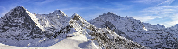 Quattro picchi e località di soggiorno di corsa con gli sci alpini in alpi svizzere Fotografia Stock Libera da Diritti