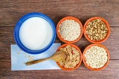 Quattro piccole ciotole con i cereali diversi e la ciotola con latte, alimento sano Immagini Stock